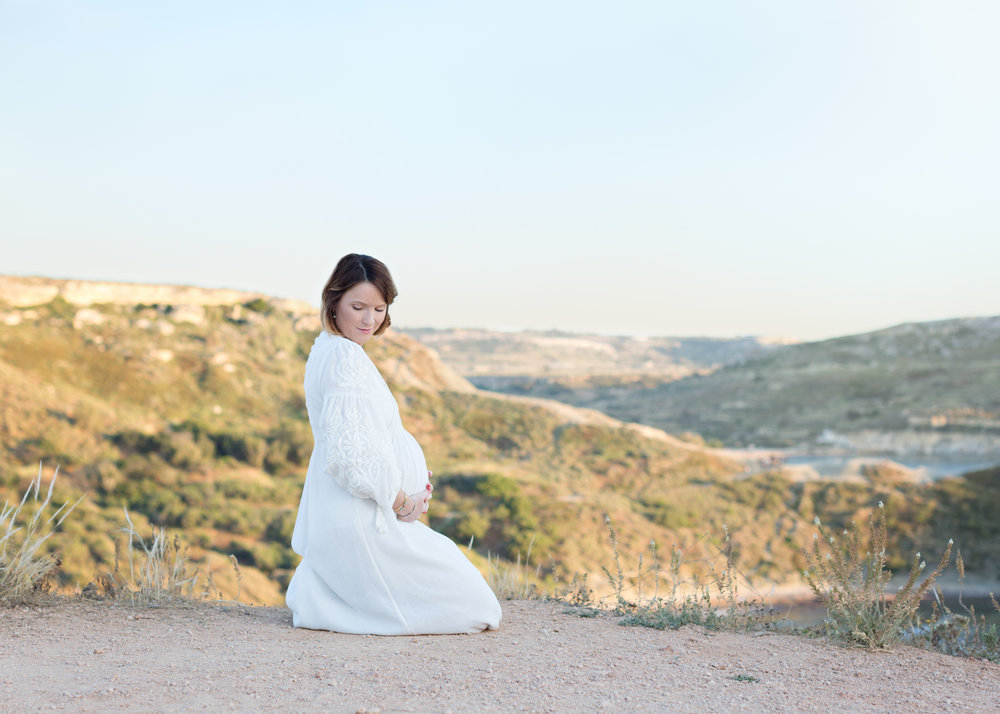 mother to be, expecting, view of mountains golden bay, unique photo shoot malta, content, bump, baby bump, hills of malta, trekking golden bay,
