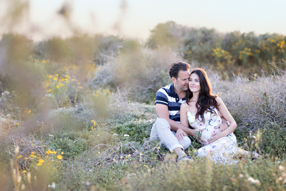 backlit maternity session in botanical garden expecting parents cuddling in gorgeous maternity dress