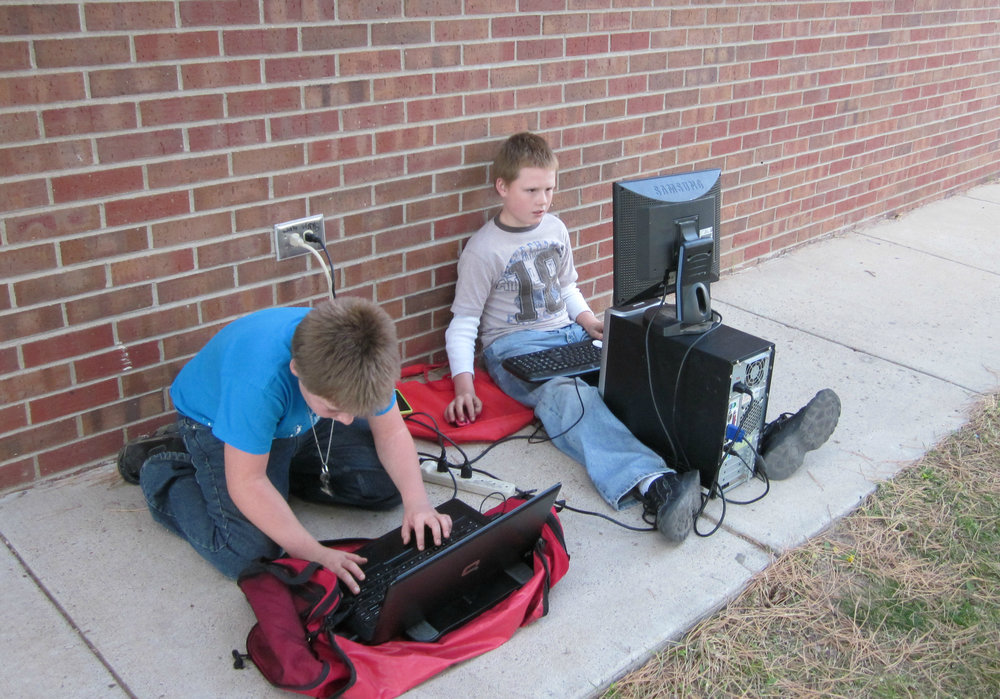 A PC can be mobile for those who are motivated enough to move it. For these two young men, the Morton County Library's public wifi was the motivation. Morton County is located in the Southwest corner of Kansas. Photo of courtesy of the Morton County Library.