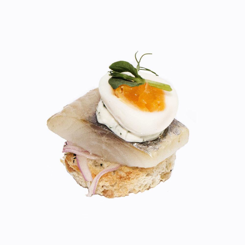Marinēta siļķe uz graudu maizes grauzdiņa, viegli marinēti sīpoli, paipalu ola un diļļu krēms
