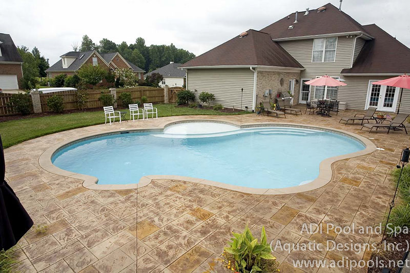 pool-with-thermal-ledge-and-stamped-concrete-pool-deck.jpg