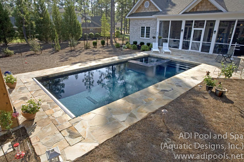 swimming-pool-and-spa-with-fieldstone-pool-deck.jpg