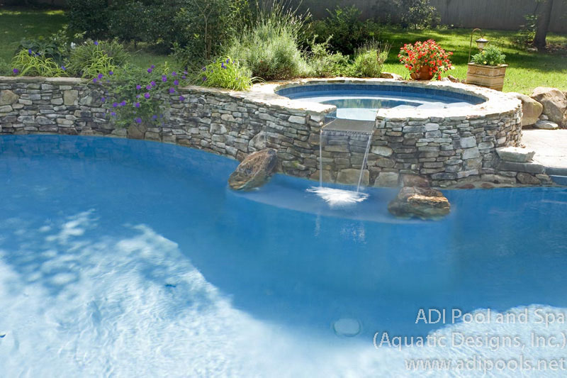 rock-spa-with-spillway-onto-pool-underwater-bench.jpg