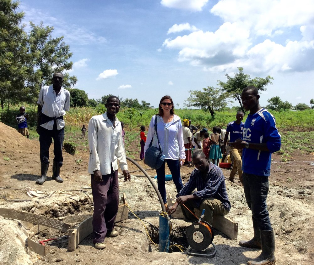 Tuktuana Director Roxanne Robbins watches as a hand pump is installed at a drill site in Busiu, Uganda.