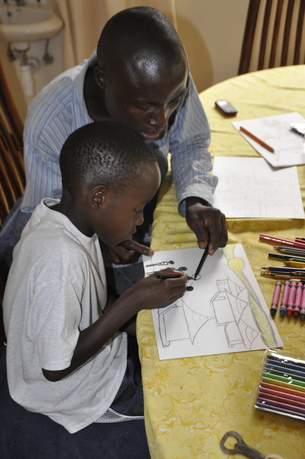 Silver Kakozzi providing art instruction for a child at Tukutana's community center in Munyonyo, Uganda.