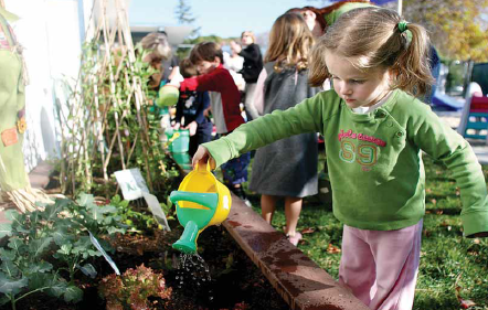 Gail L., a preschooler,waters the plants in the new raised garden bed at C.A.R. Milestones Preschool, made possible by a grant from the Garden Clubof Palo Alto. Photo byVeronica Weber.
