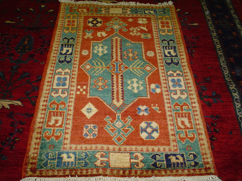 "#5) Small Kazak. 2'2"" x 3'2"" in rust-red, soft blue-green, gold and ivory."