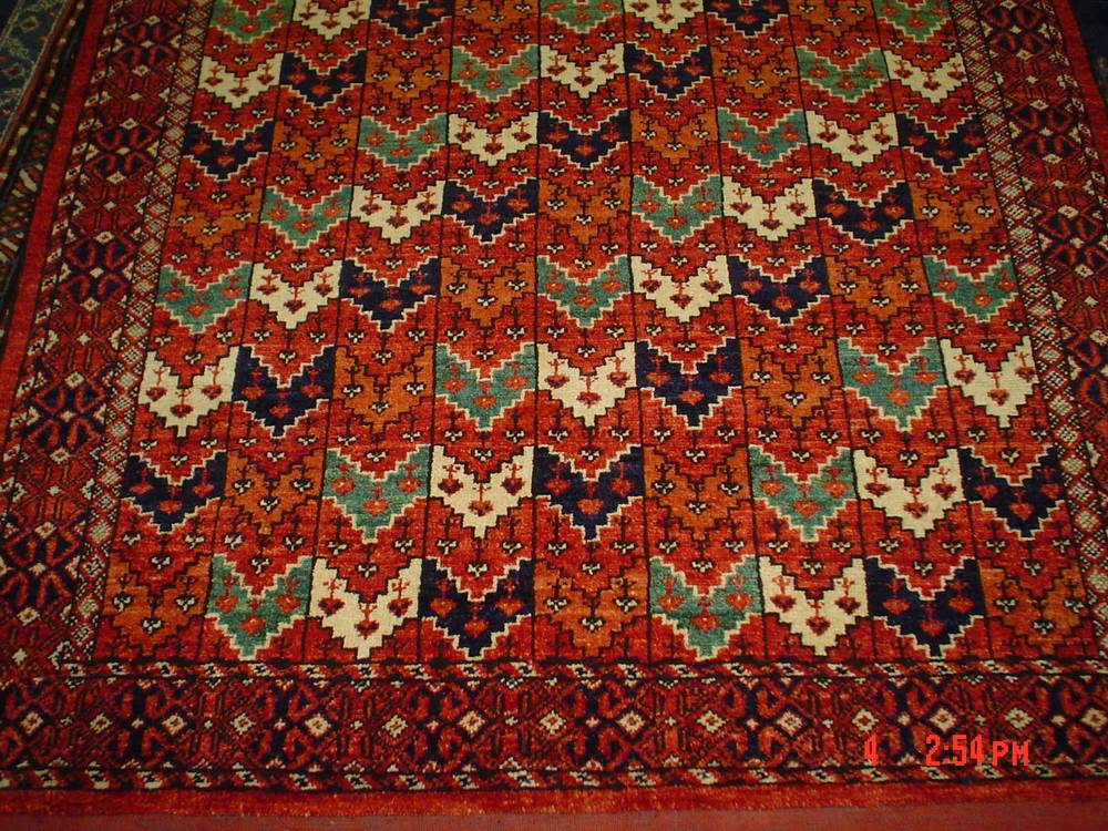 "#24) Turkoman rug close-up. 4' x 5'10"". Teal green, navy & ivory accents on a brick red field."