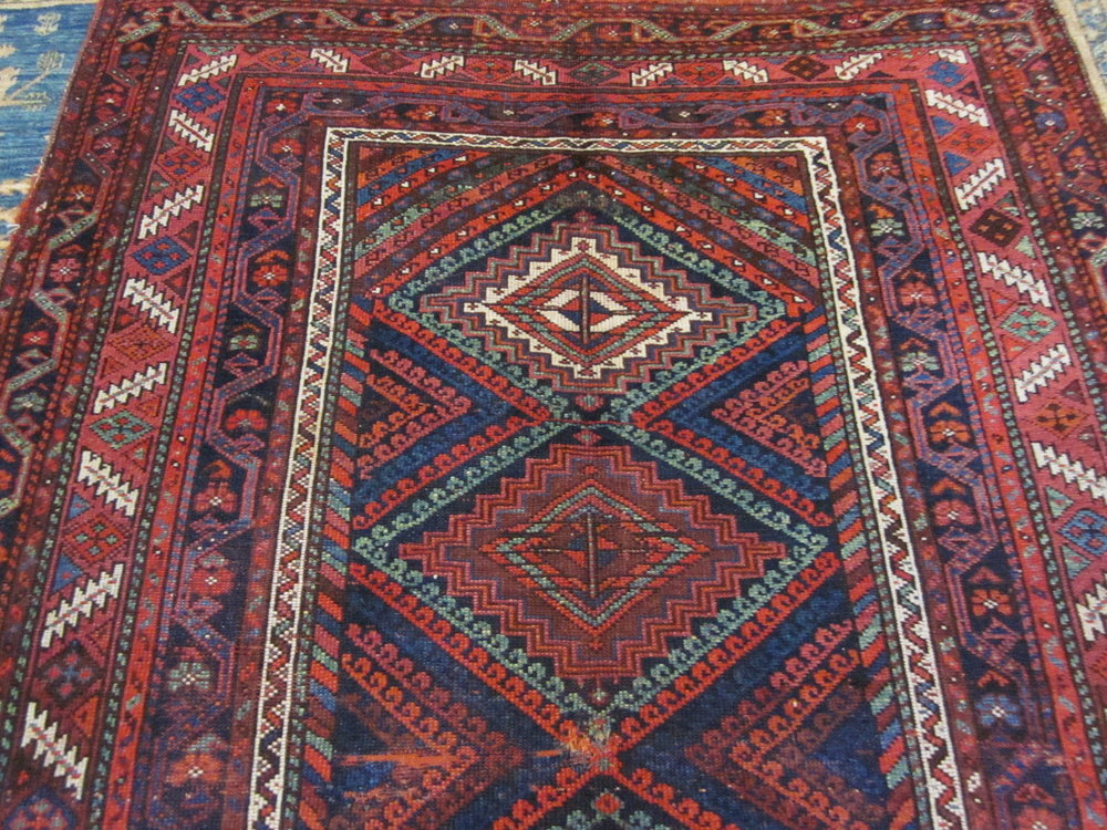Antique Kurdish tribal rug. Worn but still beautiful. On the wall in my den.