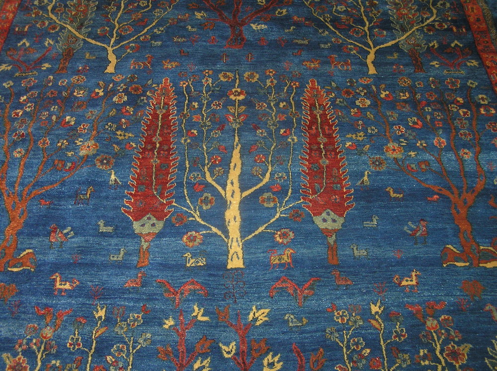 """7'9"""" x 9'11"""" Tree of Life rug in beautiful blues and reds."""