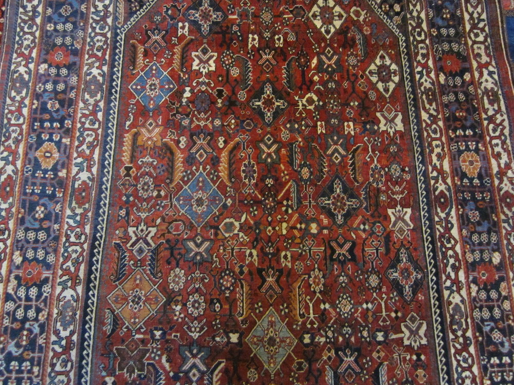 "Close-up photo, antique 5'4"" x 8'7"" Qashqai rug."