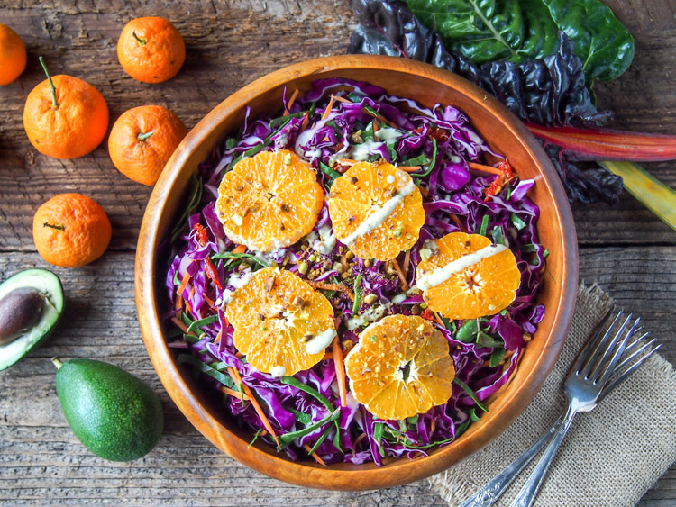 Mandarin Rainbow Salad with Avocado Tahini Dressing | vermilionroots.com. A power salad made with mandarin oranges, purple cabbage, carrots, swiss chard and sun-dried tomatoes with a creamy avocado tahini dressing.