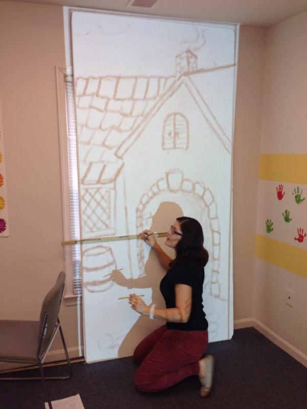 Miss Lorena tracing the sketch onto the periaktoi facing.
