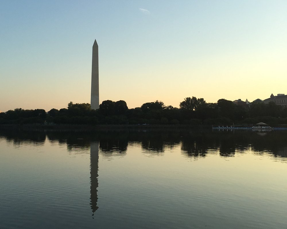 The Washington Monument reflects on the Potomac River at sunrise