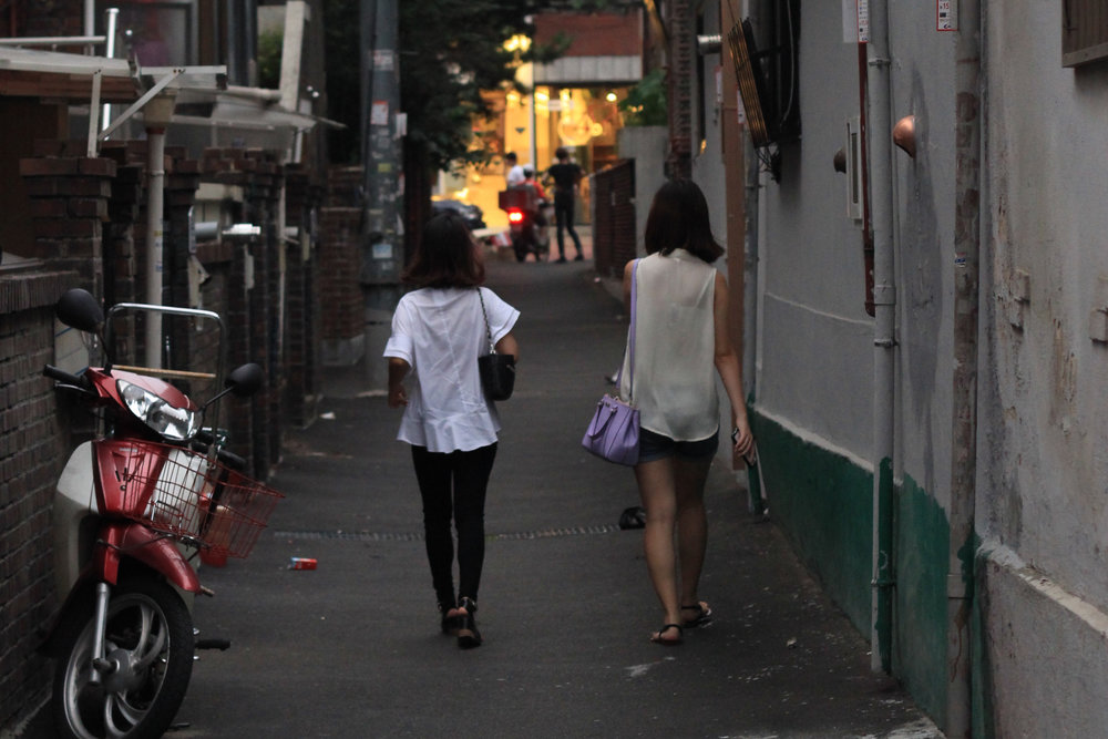 Two young girls walk down an alley together on their way to dinner.