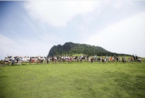 A group of students jump for a picture with an iconic Jeju attraction in the background.