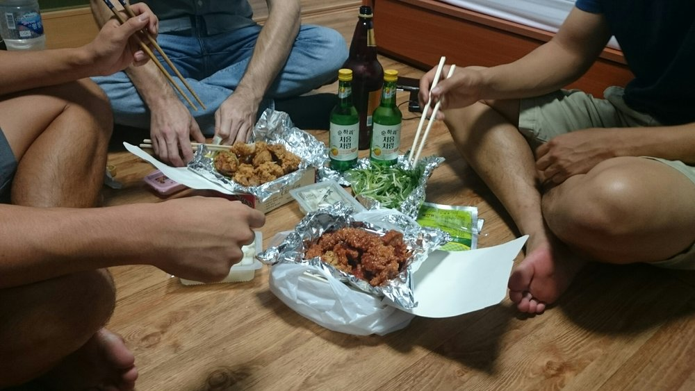 Friends enjoy Korean-style chicken and beer (Chimaek, 치맥) on the bedroom floor.