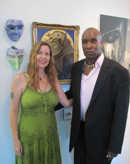 "Robyn Bellospirito and Tracy Todd Hunter, Curator of the ""Fierce"" exhibition, at Artspace Patchogue in Patchogue, NY, July 2015. The painting in the background is ""The Queen of Hearts"" and two handmade masks are to the left of that."