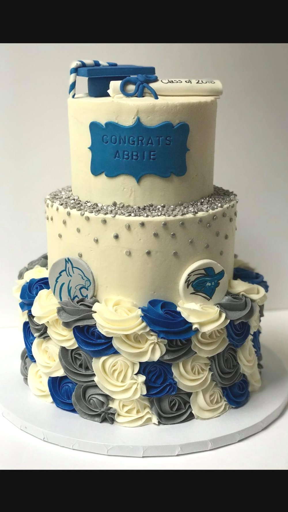 Graduate Celebration Cake - Custom designed three tiered cake that comes in a range of sizes. We include the cap, scroll, name plate, high school and college logos. Contact us for pricing as logos and details vary depending on design