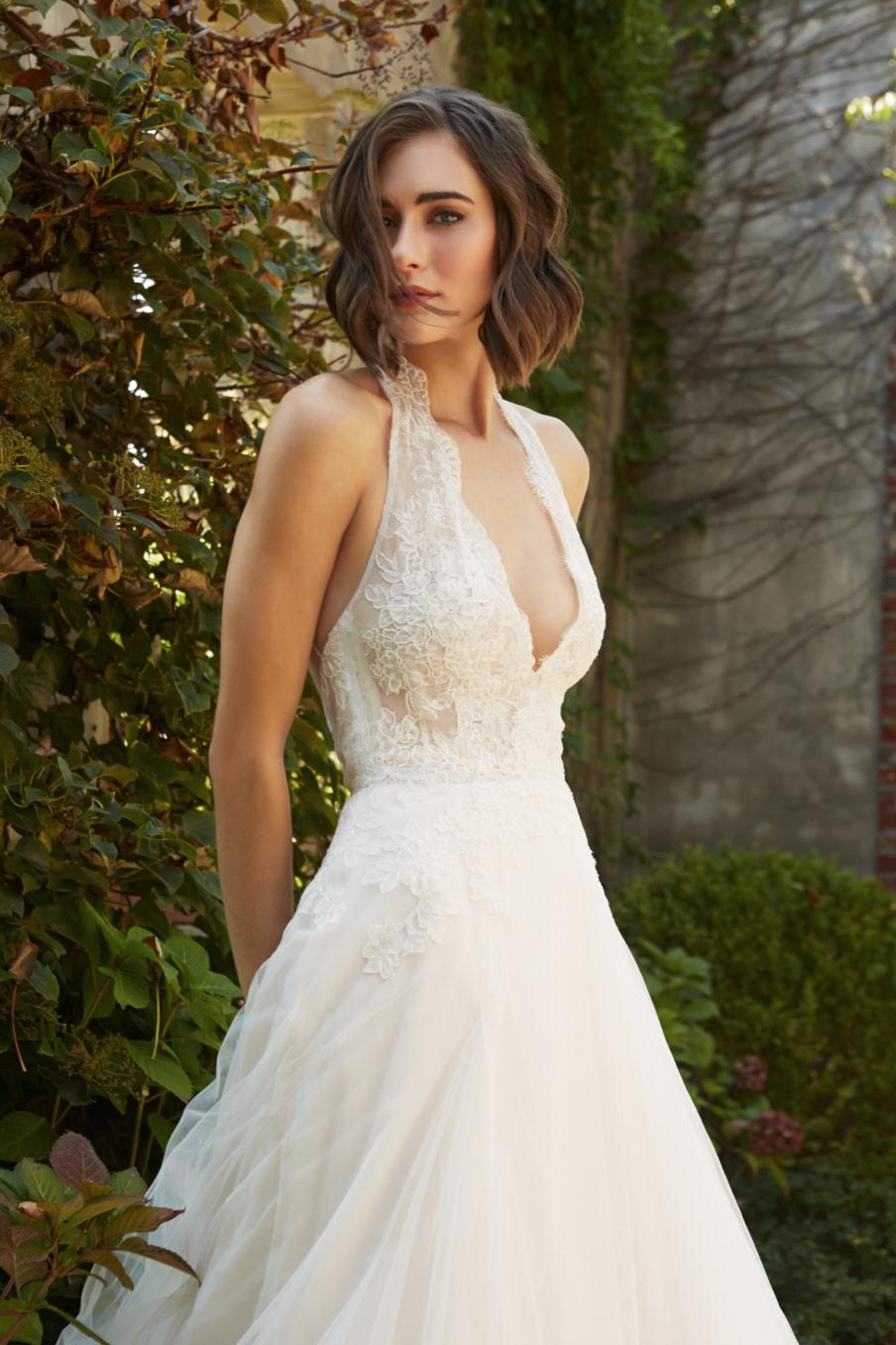 94109a538 Female fashion model wears Azalea a romantic white wedding dress of lace  and chiffon with a sexy ...