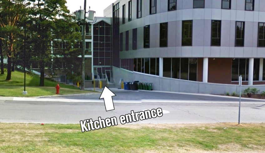 Walk around the building, up a few steps near the recycling bins, and into the door. The kitchen is on the left.