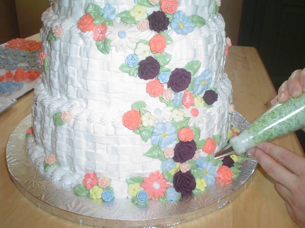 White chocolate cake with white chocolate raspberry mousse, raspberry syrup and buttercream icing. Royal icing flowers.