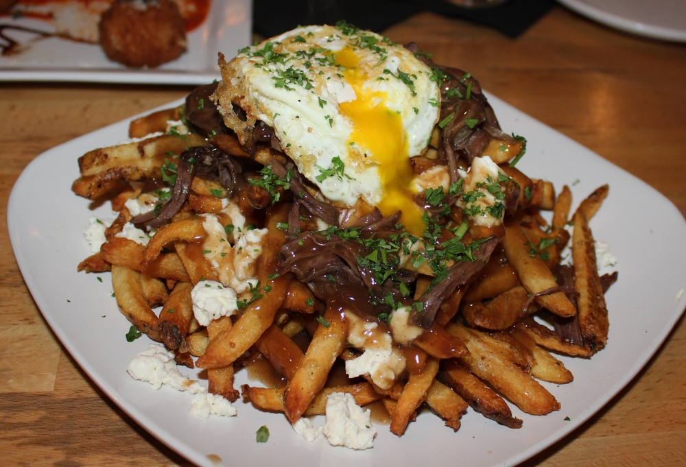 Poutine with house-cut fries, mozzarella curd, gravy, short rib, and a fried egg