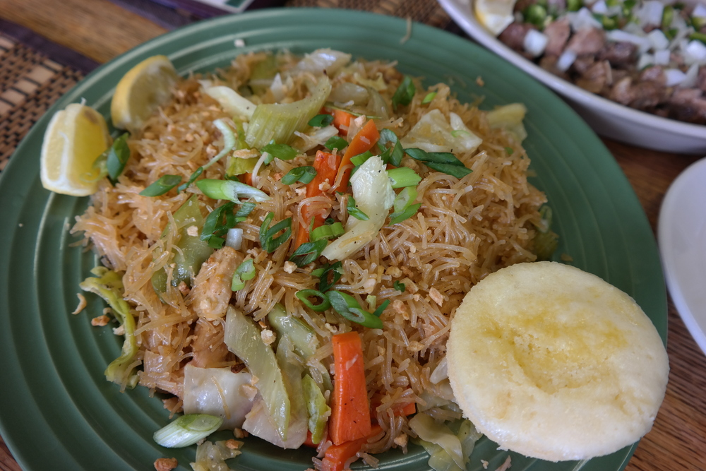 Pancit, rice noodles with vegetables and chicken and served with puto (steamed rice cake)