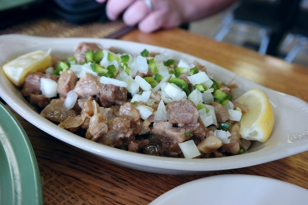 Sisig - chopped pork including pig ears and jowl sauteed with garlic and onions, garnished with jalapenos