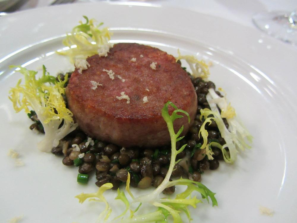 Cotechino with frisee and black lentils