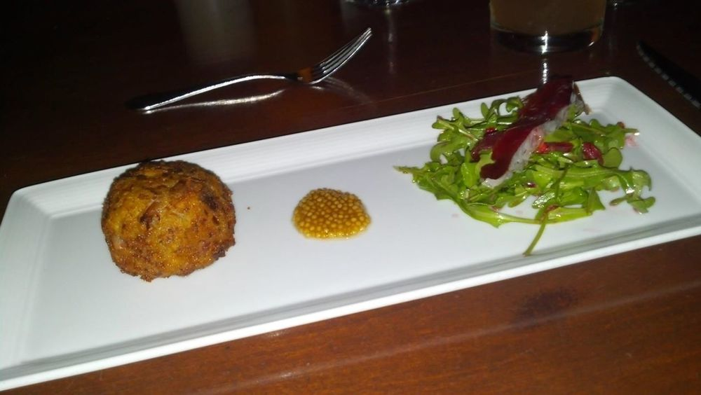 Duck confit croquette with pretzel-bread crust, confit mustard seeds, arugula, duck prosciutto, and blood orange vinaigrette
