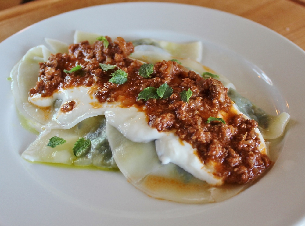 Aushak (Afghani green onion dumplings) with garlic yogurt and spiced meat sauce