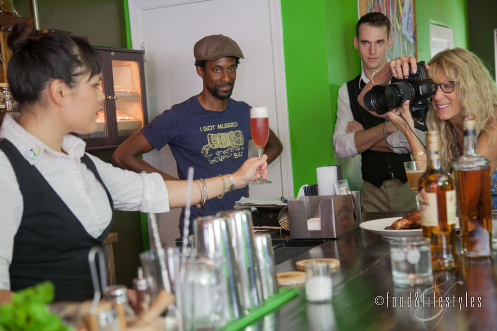 Danielle Goldtooth holds a Coconut Bramble as Debby Wolvos takes the shot and bartender Bryan Burton and owner Dwayne Allen look on.