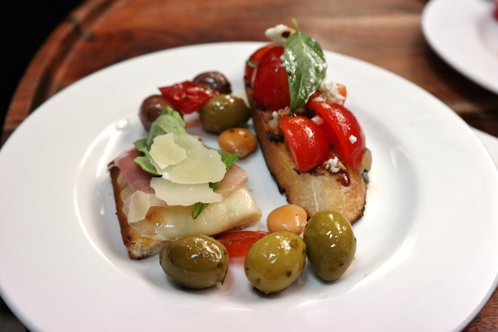 Crostini with marinated cherry tomato salad and house-smoked goat cheese, prosciutto flatbread, olives, and pickled lupini beans.