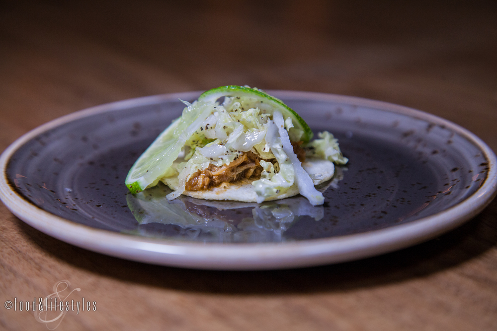 Duck confit tacos with eggplant mole, guacamole, and napa cabbage