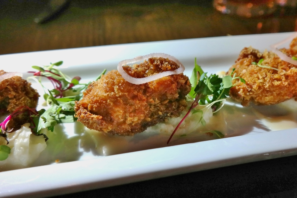 Fried oysters with creamy grits, Meyer lemon vinaigrette and microgreens