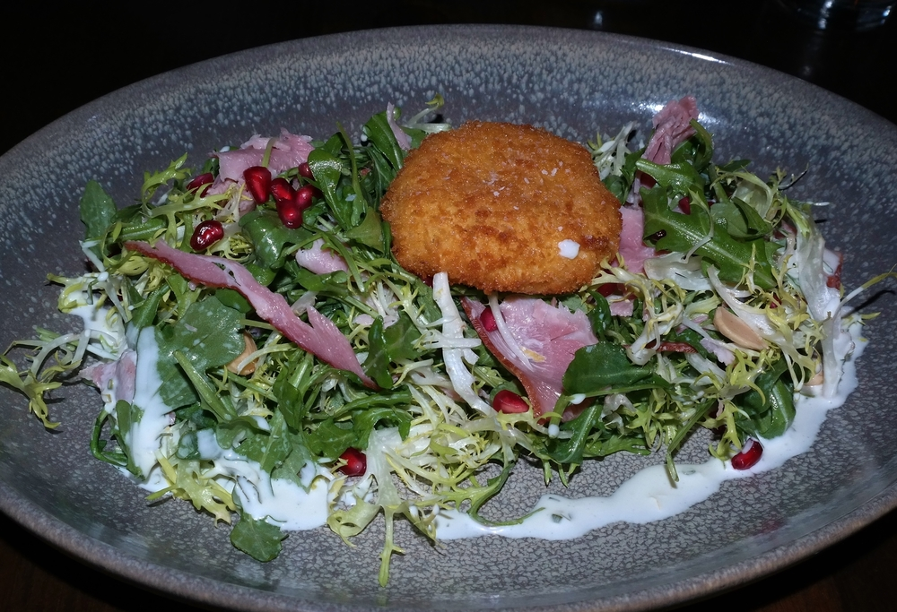 Frisée salad with crispy mozzarella, arugula, smoked ham, pomegranate seeds, and marcona almonds