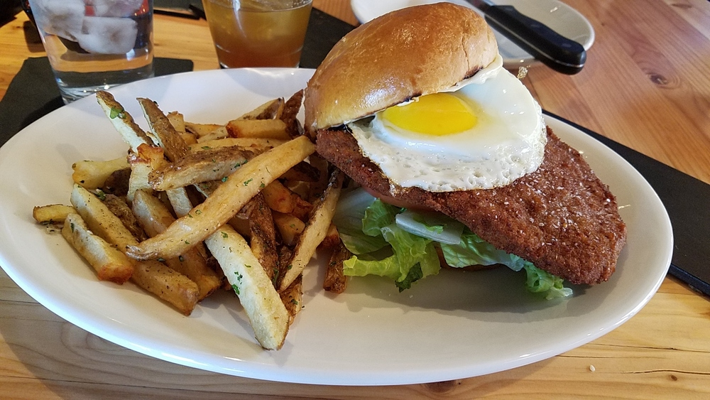Beef milanesa sandwich topped with a fried egg