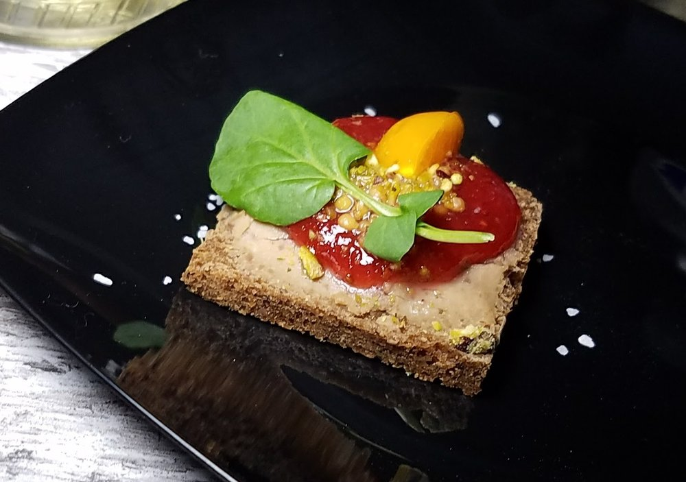 Chicken pate on rye bread with strawberry marmalade, pistachios, and pickled gooseberries