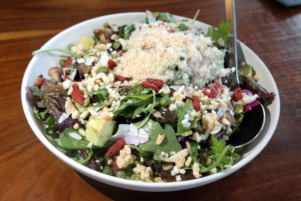 Signature salad with goji berries, avocado, puffed rice, shiitake mushrooms, shaved dried shrimp, and more