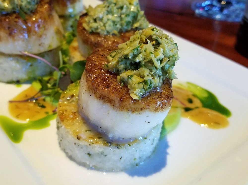 Seared scallop on polenta cake topped with herb-artichoke tapenade