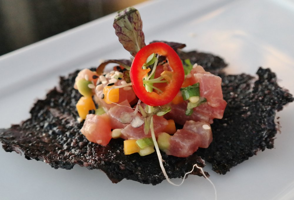 Chef Matthew Eck's yellowfin tuna with mango, avocado, yuzu, Fresno chile, and microgreens on forbidden black rice cracker at Fifth Floor Pop-Ups
