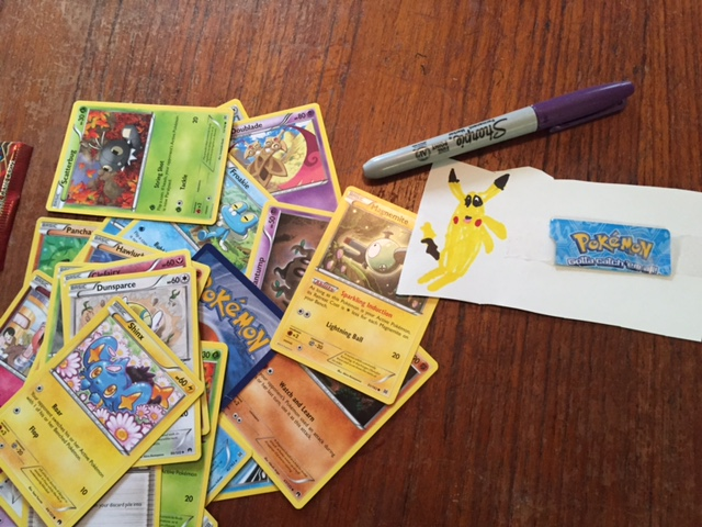 """Meanwhile, Zephyr drew his own Pikachu, and is making """"Pokémon Station"""" signs for something he's working on..."""