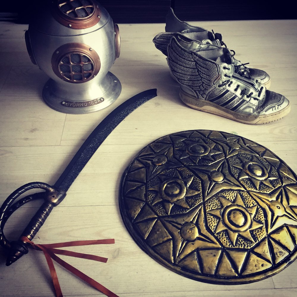 Props for the Perseus treasure hunt: Hades' helmet, Hermes' winged sandals/sneakers, Athena's shield, and Haephestus' curved blades...