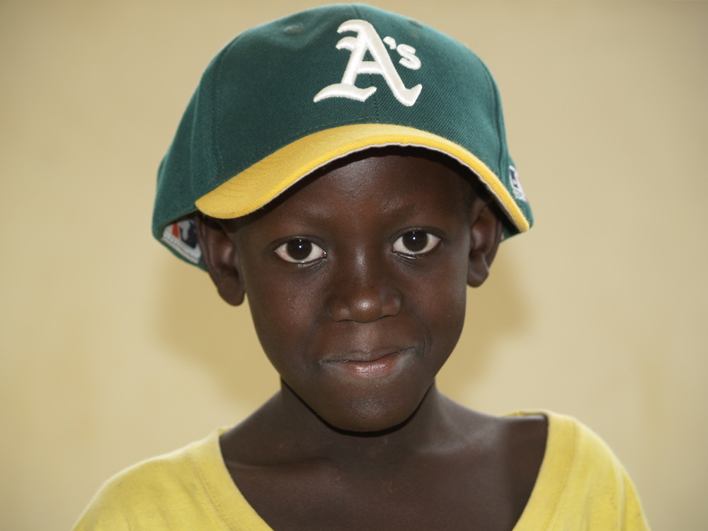 A patient in the Pediatric Ward at the Uganda Cancer Institute. He just received this baseball cap as a gift from our group, and it's a little too big for him, but he likes it just the same.