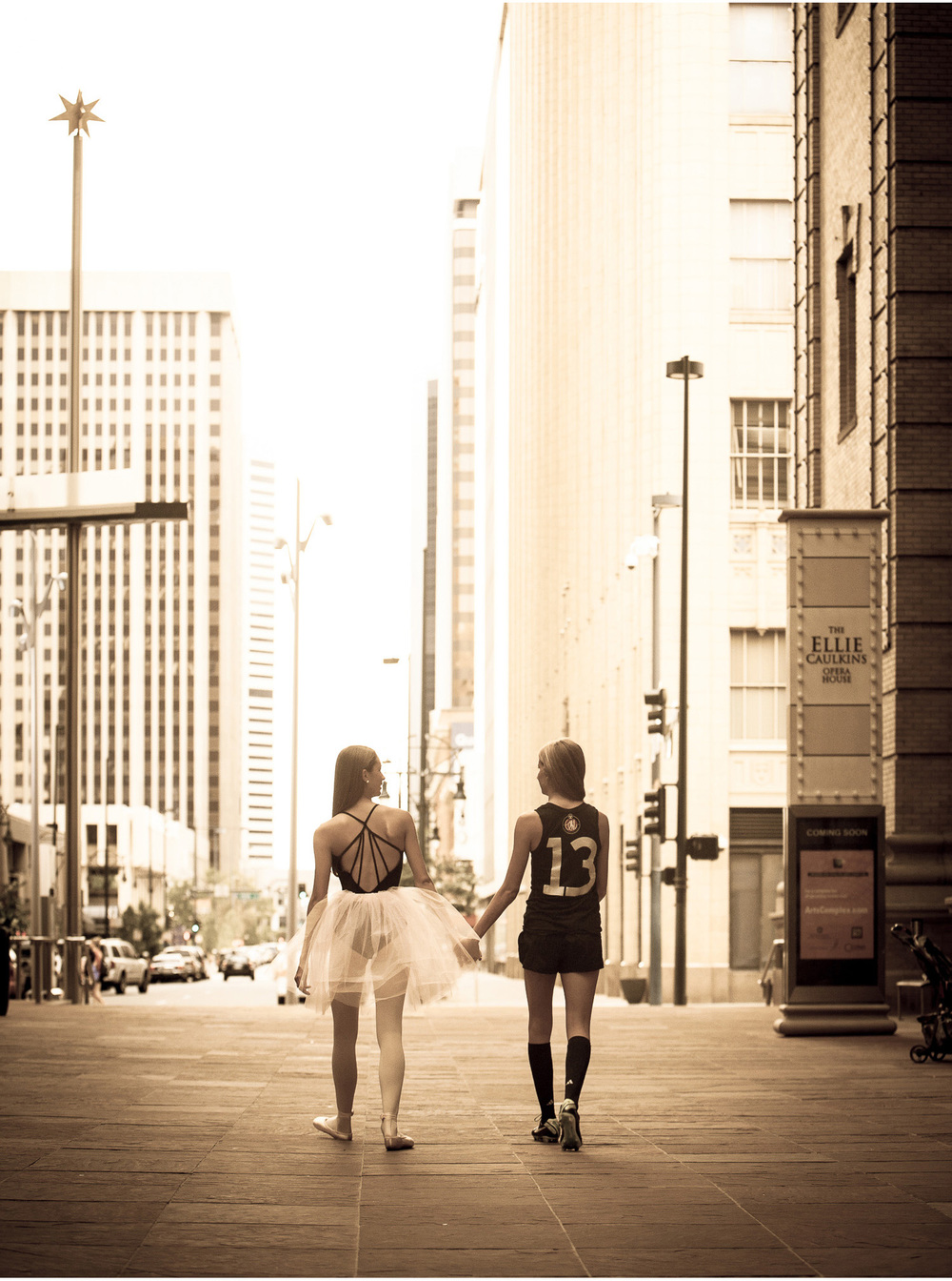 Best friends walk holding hands and walk out of the Denver Center for Performing Arts during their high school senior portrait session with photographer Jennifer Koskinen, Merritt Portrait Studio.