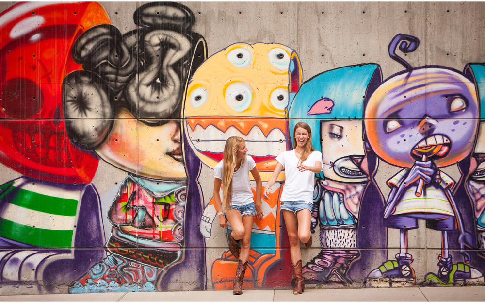 Downtown Denver, adorable best friends high school laughing during senior portrait session against colorful graffiti wall with photographer Jennifer Koskinen, Merritt Portrait Studio.