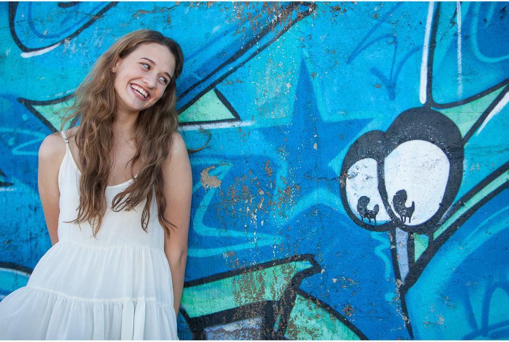 Denver high school senior pictures, gorgeous Maddie smiling at graffiti eyes | photographer Jennifer Koskinen | Merritt Portrait Studio
