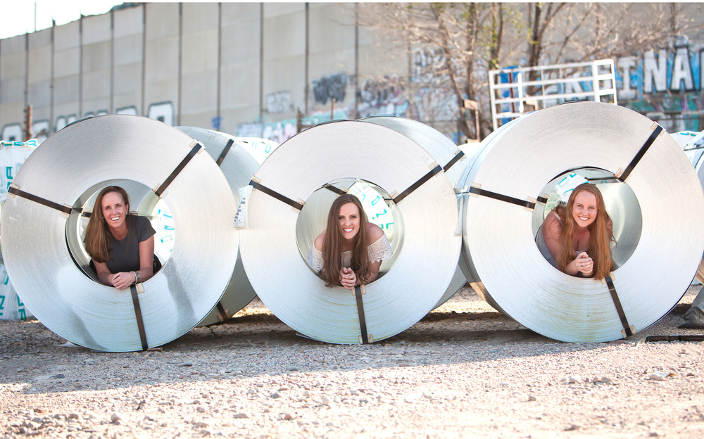 High School Senior and her mom and sister in rolls of sheet metal in a materials yard in Denver. Photographer Jennifer Koskinen, Merritt Design Photo