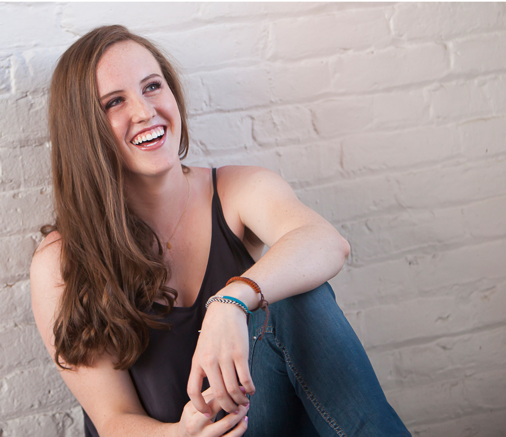 High School Senior Portrait of auburn haired girl laughing in front white-washed brick wall in Denver. Photographer Jennifer Koskinen, Merritt Design Photo